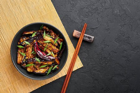 Sichuan Eggplant Stir Fry in black bowl at dark slate background. Eggplant Stir Fry is chinese cuisine dish with deep fried eggplant, chilli pepper, different sauces. Copy space. Top view