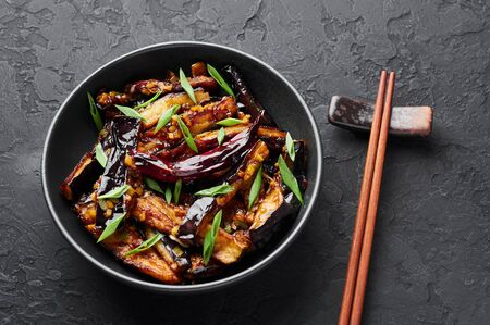 Sichuan Eggplant Stir Fry in black bowl at dark slate background. Eggplant Stir Fry is chinese cuisine dish with deep fried eggplant, chilli pepper, different sauces.