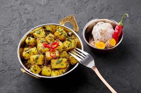 Aloo Methi in copper kadai, bowl at dark slate background. Aloo Methi is indian cuisine dish with Potato, Fenugreek and Spices. Indian Food.