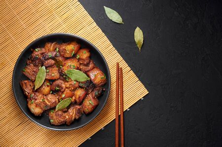 Adobo Pork in black bowl at dark slate background. Pork Adobo or Adobong Baboy is filipino cuisine dish with braised pork belly, bay leaves, soy sauce, vinegar and spices. Filipino food. Copy space