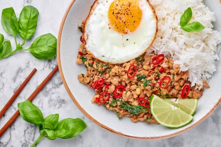 Pad Krapow Gai - Thai Basil Chicken with Rice and fried Egg on white marble background. Pad Krapow is Thai cuisine dish with minced chicken or pork meat, basil, soy and oyster sauces. Thai Food.
