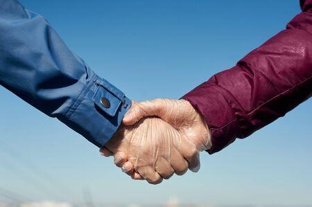 Handshake in medical gloves. Greeting in quarantine concept.