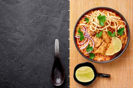 Khao Soi Gai or Thai Coconut Curry Noodle Soup in black bowl at dark slate background. Khao Soy is Thailand cuisine dish with noodles, chicken meat, red chillies paste and spices. Copy space