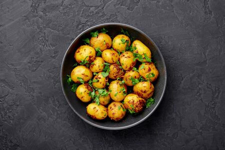 Jeera Aloo in black bowl on dark slate background. Jeera Aloo is indian cuisine dish with baby potatoes, jeera seeds and coriander. Copy space