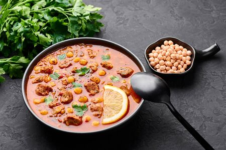 Moroccan Harira Soup in black bowl at dark slate bakcground. Harira is Moroccan Cuisine dish with lamb or beef meat, chickpeas, lentils, tomatoes and ciliantro. Ramadan Iftar Food. Copy space
