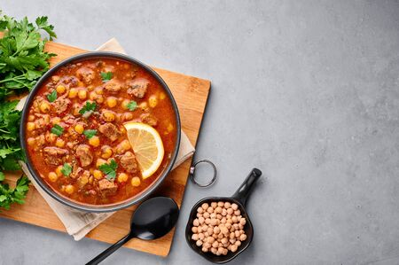 Moroccan Harira Soup in black bowl at grey concrete table top. Harira is Moroccan Cuisine dish with lamb or beef meat, chickpeas, lentils, tomatoes, ciliantro. Ramadan Iftar Food. Copy space. Top view