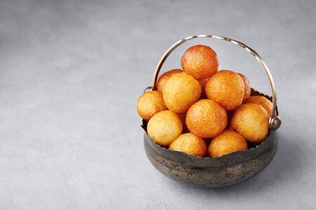 Loukoumades, luqaimat or lokma in vintage metal cup on grey concrete background. Loukoumades is eastern cuisine donunts popular during Ramazan. Popular Ramadan Food. Iftar and Suhur sweets. Copy space