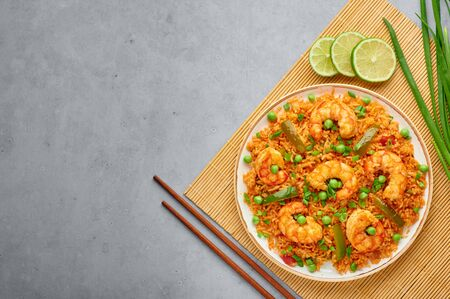 Thai Tom Yum Fried Rice or Prawn Biryani in white plate on gray concrete backdrop. Tom Yum Fried Rice is Thailand cuisine dish with jasmine rice, shrimps and vegetables. Thai Food. Top view Banque d'images