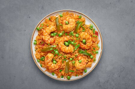 Thai Tom Yum Fried Rice or Prawn Biryani in white plate on gray concrete backdrop. Tom Yum Fried Rice is Thailand cuisine dish with jasmine rice, shrimps and vegetables. Thai Food. Top view