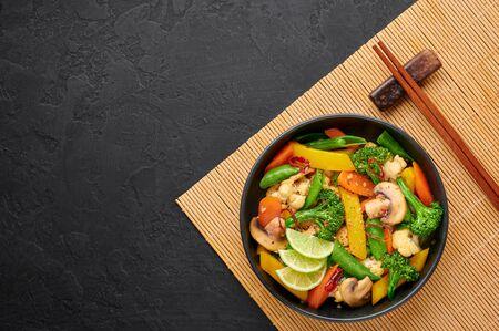 Pad Pak Ruam or Veg Thai Stir-Fried Vegetables in black bowl on dark slate backdrop. Pad Pak is thailand cuisine vegetarian dish with mix of vegetables and sauces. Thai Food. Copy space, Tip view Standard-Bild