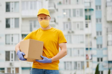 Delivery Man employee in yellow uniform cap, t-shirt, face mask and gloves holds a cardboard box package on building backdrop. Safety delivery quarantine service in covid-19 virus pandemic period.