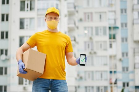 Delivery Man employee in yellow uniform cap, t-shirt, face mask and gloves holds a cardboard box package shows complete sign on the phone. Safety delivery quarantine service in covid-19 virus pandemic Zdjęcie Seryjne