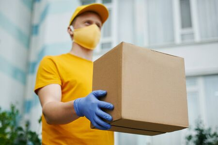Delivery Man worker in yellow uniform cap, t-shirt, face mask and gloves holds a cardboard box package on building backdrop. Safety delivery quarantine service in covid-19 virus pandemic period.