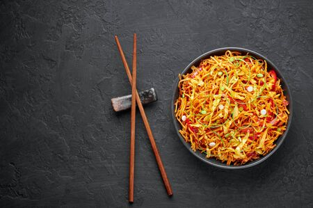 Chinese Bhel in black bowl on dark slate table top. Chinese Bhel is Indo-Chinese cuisine street food dish of deep fried hakka noodles, vegetables and schezwan sauce Stock Photo