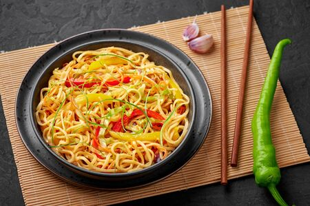 Chilli Garlic Hakka Noodles in black bowl on dark slate tabpe top. Indo-Chinese vegetarian cuisine dish. Indian veg noodles with vegetables. Classic Asian meal