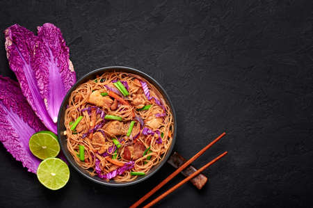Pancit Bihon in black bowl on dark slate table top. Filipino cuisine noodles dish with pork belly, chicken, vegetables. Asian food. Top view. Copy space Reklamní fotografie