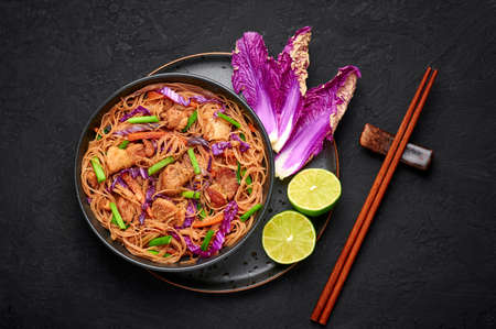 Pancit Bihon in black bowl on dark slate table top. Filipino cuisine noodles dish with pork belly, chicken, vegetables. Asian food. Top view