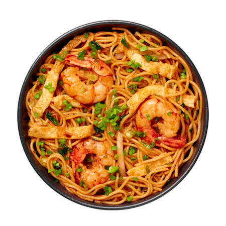 Mie Goreng in black bowl isolated on white. Indonesian cuisine prawn noodles and vegetables stir fired dish. Asian food.