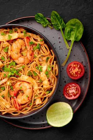 Mie Goreng in black bowl on dark slate table top. Indonesian cuisine prawn noodles and vegetables stir fired dish. Asian food. Top view Stockfoto