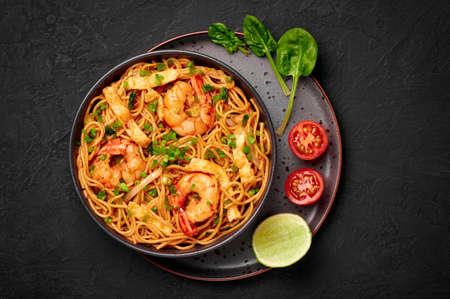 Mie Goreng in black bowl on dark slate table top. Indonesian cuisine prawn noodles and vegetables stir fired dish. Asian food. Top view
