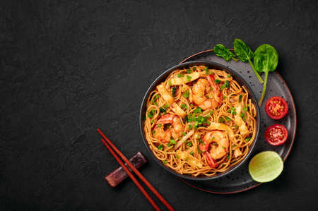 Mie Goreng in black bowl on dark slate table top. Indonesian cuisine prawn noodles and vegetables stir fired dish. Asian food. Top view. Copy space Stockfoto