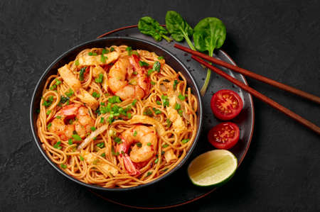 Mie Goreng in black bowl on dark slate table top. Indonesian cuisine prawn noodles and vegetables stir fired dish. Asian food.