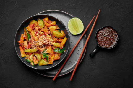 Penang Rojak in black bowl on dark slate table top. Malaysian or indonesian cuisine fruits and vegetables salad dish. Asian Food. Top view