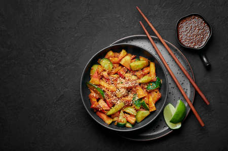 Penang Rojak in black bowl on dark slate table top. Malaysian or indonesian cuisine fruits and vegetables salad dish. Asian Food. Top view. Copy space