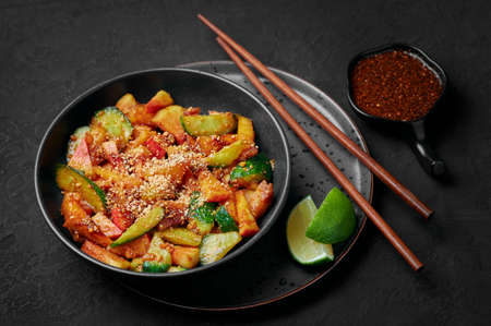 Penang Rojak in black bowl on dark slate table top. Malaysian or indonesian cuisine fruits and vegetables salad dish. Asian Food.