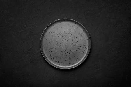 An empty black flat plate on dark slate table top. Rough ceramic plate background with copy space Banque d'images