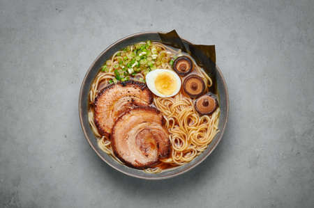 A Shoyu Ramen in gray bowl on concrete table top. Japanese cuisine meat noodle soup with chashu pork. Asian food. Top view