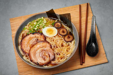 A Shoyu Ramen in gray bowl on concrete table top. Japanese cuisine meat noodle soup with chashu pork. Asian food Reklamní fotografie