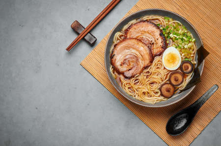 A Shoyu Ramen in gray bowl on concrete table top. Japanese cuisine meat noodle soup with chashu pork. Asian food. Top view. Copy space Reklamní fotografie