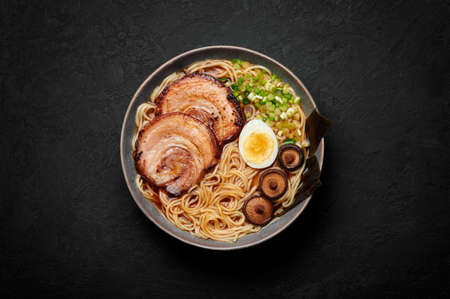 A Shoyu Ramen in gray bowl on black slate table top. Japanese cuisine meat noodle soup with chashu pork. Asian food