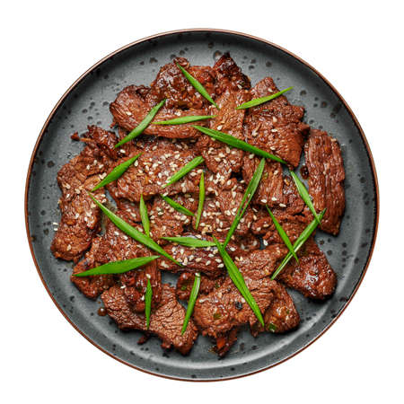 Beef Bulgogi on black plate isolated on white. Korean cuisine meat dish with sauce and kiwi. Traditional asian food. Top view