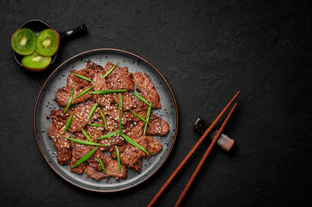 Beef Bulgogi on black plate on dark slate table top. Korean cuisine meat dish with sauce and kiwi. Traditional asian food. Top view. Copy space