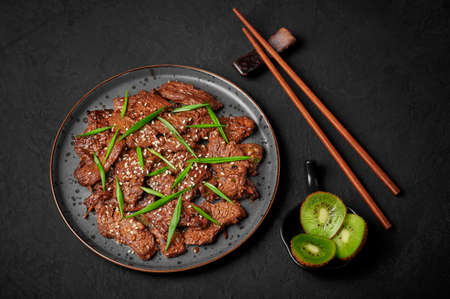 Beef Bulgogi on black plate on dark slate table top. Korean cuisine meat dish with sauce and kiwi. Traditional asian food Reklamní fotografie