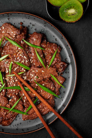 Beef Bulgogi on black plate on dark slate table top. Korean cuisine meat dish with sauce and kiwi. Traditional asian food. Top view