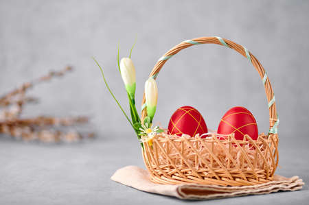 Two red painted Easter eggs in the wicker basket on gray table top with pussy willow branches on backdrop