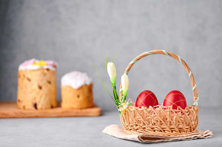 Two red painted Easter eggs in the wicker basket on gray table top with two easter cakes on backdrop