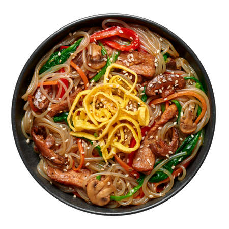 Japchae in black bowl isolated on white. Korean cuisine glass chapchae noodles dish with vegetables and meat. Asian traditional food. Authentic meal. Top view