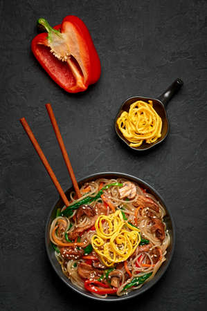 Japchae in black bowl on dark slate table top. Korean cuisine glass chapchae noodles dish with vegetables and meat. Asian traditional food. Authentic meal. Top view