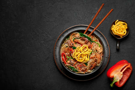 Japchae in black bowl on dark slate table top. Korean cuisine glass chapchae noodles dish with vegetables and meat. Asian traditional food. Authentic meal. Top view. Copy space