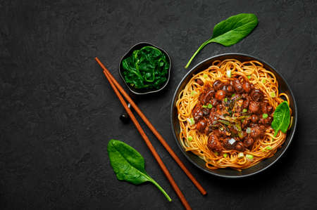 Bakmi or Mie Ayam in black bowl on dark slate table top. Indonesian cuisine noodles meat dish. Traditional asian food and meal. Top view. Copy space Reklamní fotografie