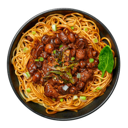 Bakmi or Mie Ayam in black bowl isolated on white. Indonesian cuisine noodles meat dish. Traditional asian food and meal. Top view
