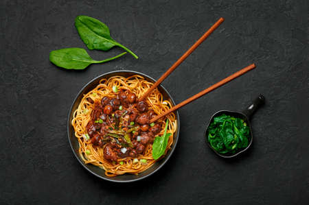 Bakmi or Mie Ayam in black bowl on dark slate table top. Indonesian cuisine noodles meat dish. Traditional asian food and meal. Top view