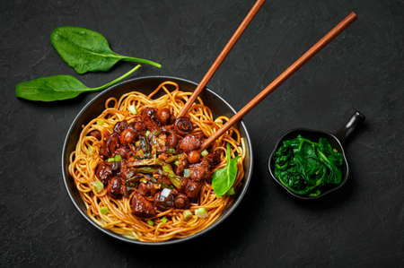 Bakmi or Mie Ayam in black bowl on dark slate table top. Indonesian cuisine noodles meat dish. Traditional asian food and meal.