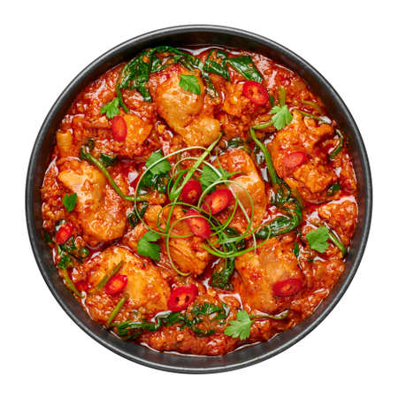 Chicken Vindaloo with spinach in black bowl isolated on white. Indian cuisine meat chilli curry dish. Authentic asian food.