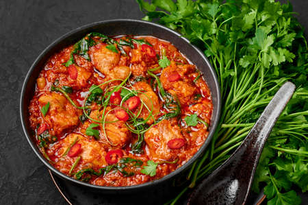 Chicken Vindaloo with spinach in black bowl on dark slate table top. Indian cuisine meat chilli curry dish. Authentic asian food. Reklamní fotografie