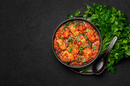 Chicken Vindaloo with spinach in black bowl on dark slate table top. Indian cuisine meat chilli curry dish. Authentic asian food. Top view. Copy space